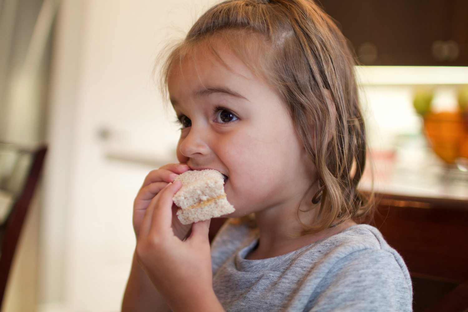 toddler eating sandwich